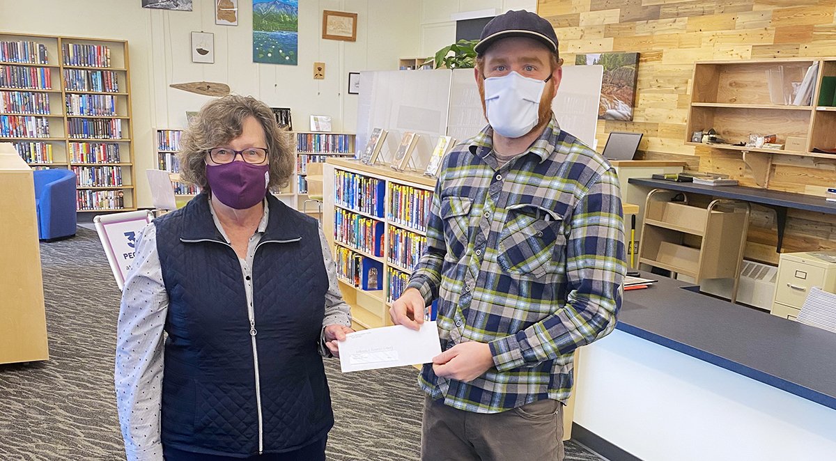 Penobscot County Commissioner Laura Sanborn holds a check with Millinocket Library